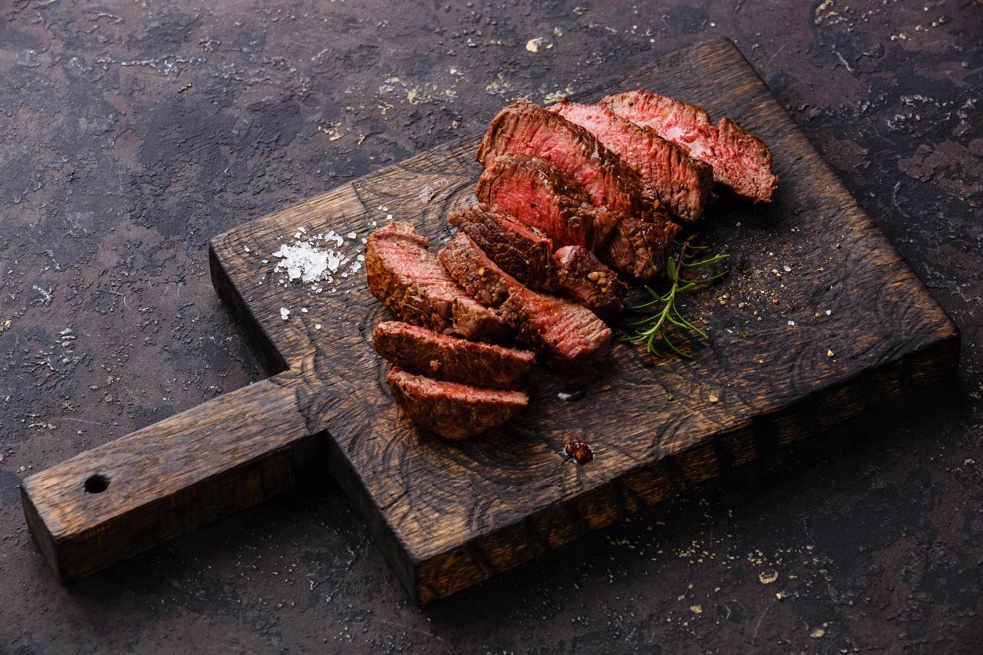 Carne a la parrilla sobre tabla de madera